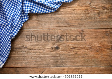 Blue checkered tablecloth on wooden table - stock photo