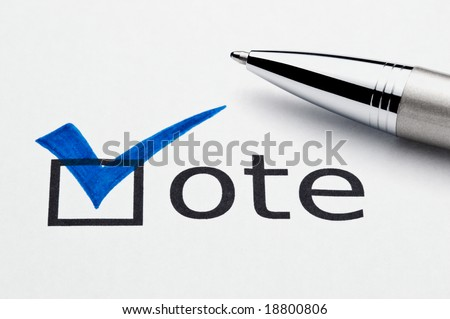 Blue checkmark on vote checkbox, pen lying on ballot paper. Concept for voter registration and participation in elections, or for voting blue/democrat; not an isolation, paper texture is visible - stock photo