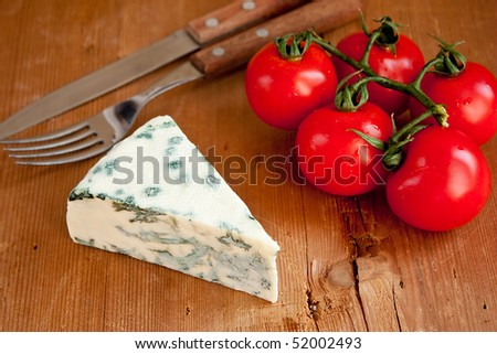Blue cheese and tomatoes on wooden table