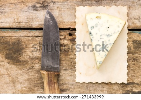 Blue cheese background with copyspace. Piece of cheese with old knife on wooden table - stock photo