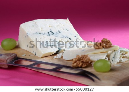 Blue cheese on cutting board with walnuts and grapes - stock photo