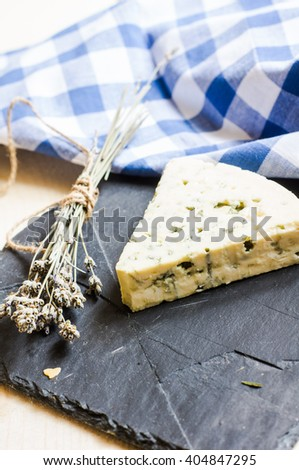 Blue cheese on rustic background with herbs and bright blue napkin - stock photo
