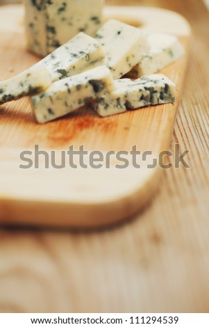 Blue cheese on wood plate - stock photo