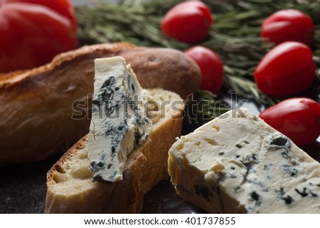 Blue cheese with french baguette, tomato and herbs on black marble table. Traditional snacks in France and Italy closeup. - stock photo