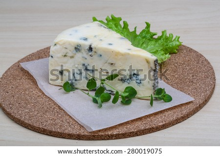 Blue cheese with oregano and salad leaves on wood background - stock photo