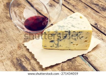 Blue cheese with overturned glass of wine on wooden table. Restaurant vintage menu background. Warm color toned image - stock photo