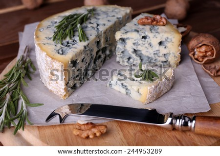 Blue cheese with sprigs of rosemary and nuts on board with knife and wooden table background - stock photo