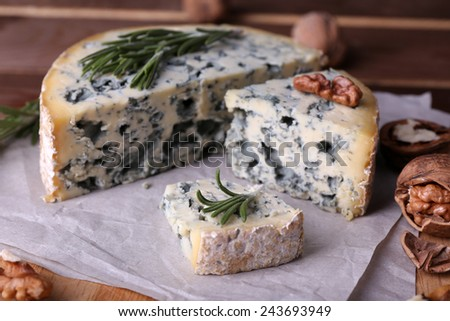 Blue cheese with sprigs of rosemary and nuts on board with sheet of paper and wooden table background - stock photo
