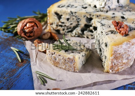 Blue cheese with sprigs of rosemary and nuts on sheet of paper and color wooden table background - stock photo