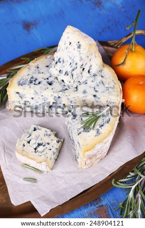 Blue cheese with sprigs of rosemary and oranges on metal tray with sheet of paper and color wooden table background - stock photo