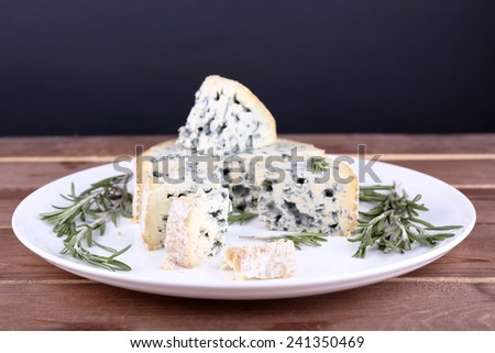 Blue cheese with sprigs of rosemary on plate on wooden table and dark background - stock photo