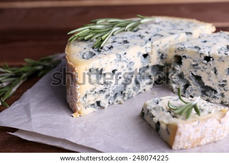 Blue cheese with sprigs of rosemary on sheets of paper and wooden table background - stock photo