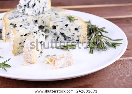 Blue cheese with sprigs of rosemary on wooden board background - stock photo