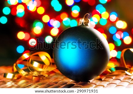 Blue Christmas ball on the background of blurred lights garlands. - stock photo