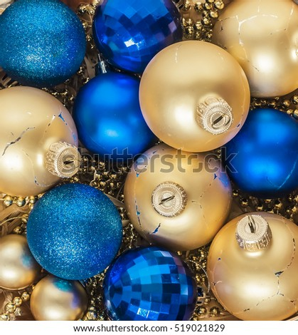 blue Christmas balls and gold, beads lie in a wooden basket top view of vintage style.
