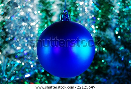 Blue Christmas bauble against tinsel background - stock photo