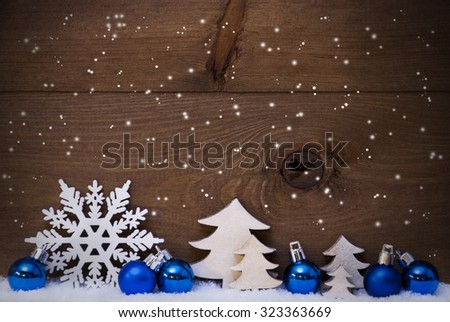 Blue Christmas Decoration On White Snow. Christmas Tree Balls, Snowflakes And Christmas Tree.  Copy Space For Advertisement. Rustic, Vintage Brown Wooden Background.