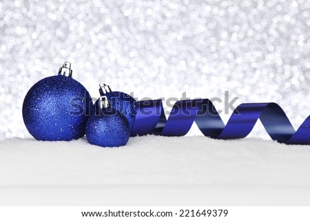 Blue Christmas decorations on snow close-up - stock photo