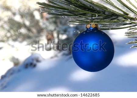 blue christmas ornament in snowy pine tree - stock photo