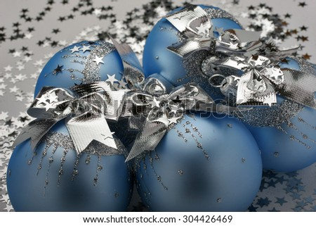 Blue Christmas ornaments for the Christmas tree with sparkles in the form of stars and  silver ribbons. New Year mood. Blue and silver christmas decoration isolated on white background. Macro. - stock photo