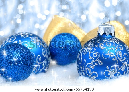 Blue christmas tree balls and golden ribbon over blurry background. Shallow depth of field - stock photo