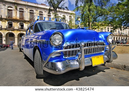 Blue classic american car in havana street with eroded buildings in the background, cuba - stock photo