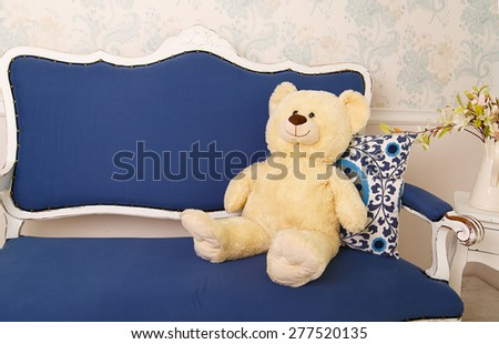 Blue classical style sofa couch with white teddy bear in vintage room  - stock photo