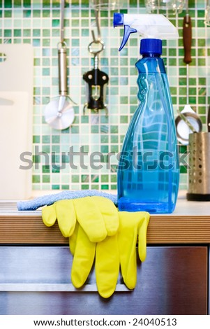 Blue cleaning spray bottle on kitchen table - stock photo