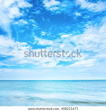 Blue clear sea and sky with white clouds - stock photo