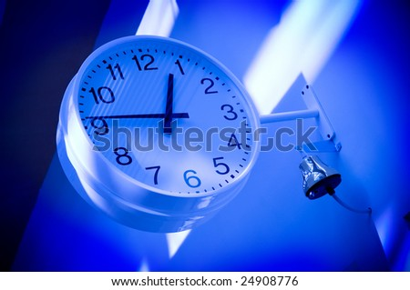 Blue clock on wall with school bell ready to ring in a school. Hurry up students! - stock photo