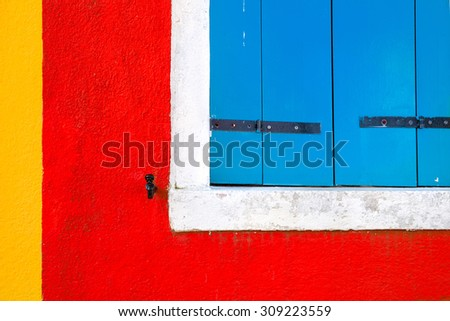 Blue closed window on colorful house wall located in Burano, Venice