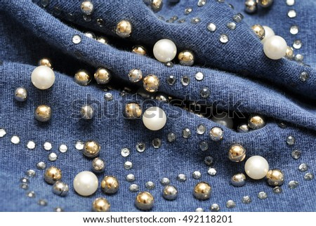 Blue cloth decorated with multicolor crystals. Background. Macro with extremely shallow dof