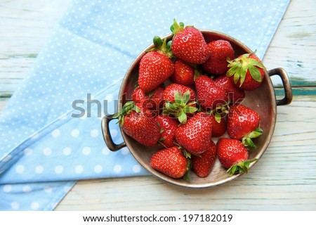 blue cloth with a bowl of fresh strawberries on a wooden table - stock photo