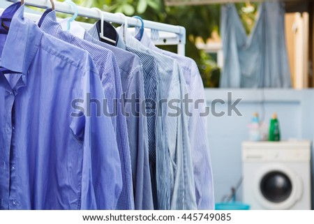 Blue clothes wait for dry with washing machine background