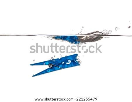 Blue Clothespin splashing and sinking underwater - stock photo