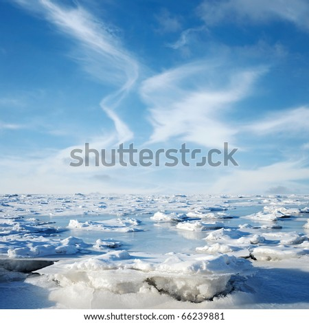 Blue clouds and frozen water. Winter landscape - stock photo