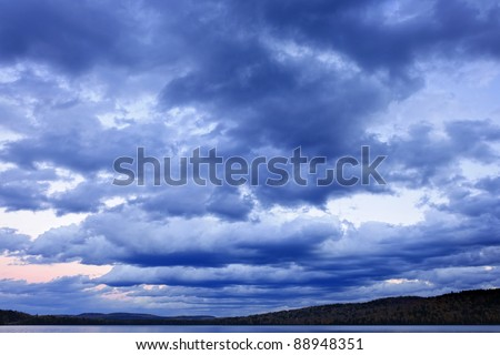 Blue cloudy dramatic sky at sunset over forest wilderness in Algonquin Park, Canada - stock photo