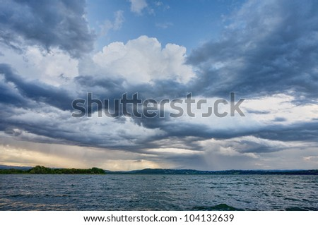 Blue cloudy dramatic sky to lake - stock photo