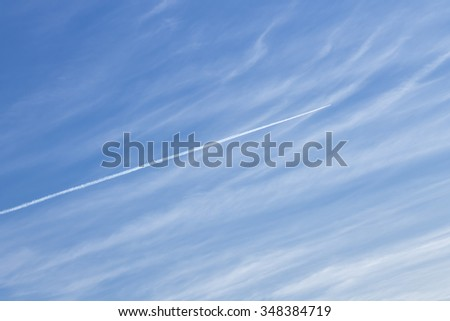 Blue cloudy sky with white path of airplane