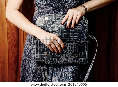 Blue clutch in hands - stock photo