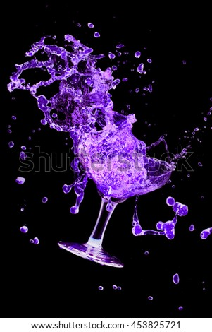 Blue cocktail glass splash out on a black background.  - stock photo