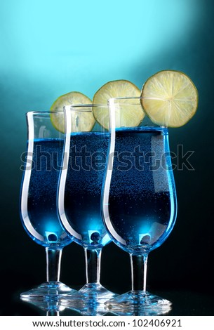 Blue cocktail in glasses with lime on blue background - stock photo