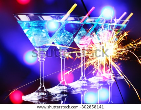 Blue cocktail in martini glasses on bright background - stock photo