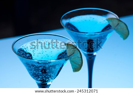 Blue cocktail in martini glasses on the bar table - stock photo