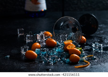 Blue cocktail in martini glasses with ice and Kumquat on black background - stock photo