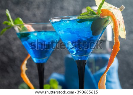 Blue cocktail with ice and mint in martini glasses on gray background - stock photo