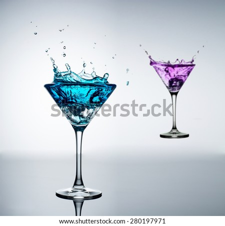 blue cocktail with splashes on white background - stock photo