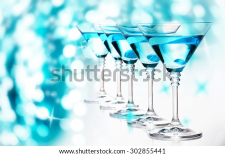 Blue cocktails in martini glasses on bright background - stock photo