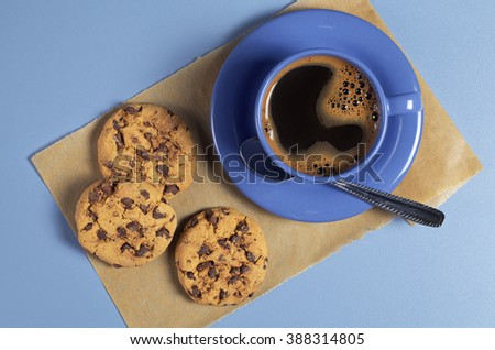 Blue coffee cup and chocolate cookies on the table, top view