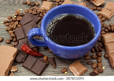 Blue coffee cup, foam, a piece of chocolate bars tied with a ribbon rustic. Milk and dark chocolate. Coffee beans. The wooden surface of the table. Chili pepper. Cayenne. Chocolate bar - stock photo